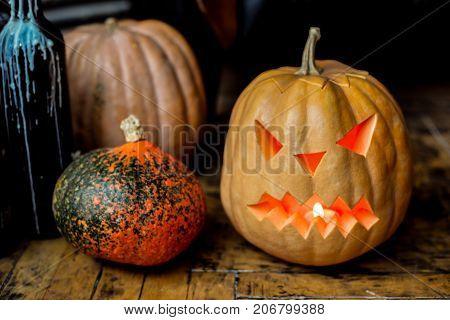 Family of Halloween pumpkin head jack lantern near candlestick bottles on black leather armchair background.