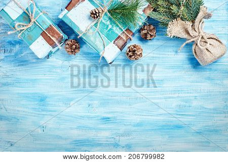Top view of Christmas background on blue wooden board with fir cones and gift boxes forming top rim. Copy space.