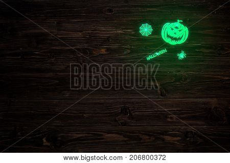 Halloween Glowing Phosphoric Jack-o'-lantern Over Wooden Table Background. Neon Light
