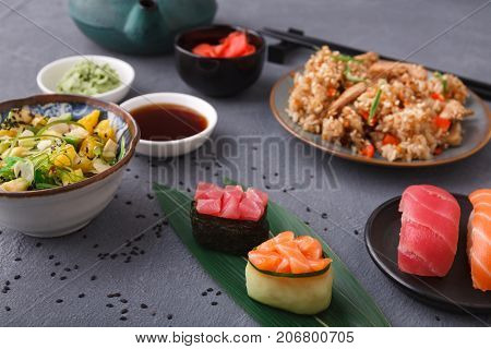 Asian cuisine concept. Beef teriyaki with rice, avocado and orange salad with seaweed, almond flakes and black sesame and sushi. Set with chopsticks, ginger, soy, wasabi on dark background, closeup