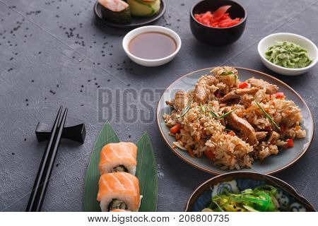Asian cuisine concept. Beef teriyaki with rice, avocado and orange salad with seaweed, almond flakes and black sesame and sushi. Set with chopsticks, ginger, soy, wasabi on dark background