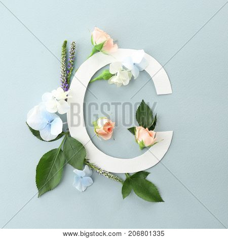 Composition with letter C and beautiful flowers on color background