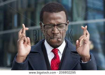 Handsome African American Business Man With Crossed Fingers And Closed Eyes Asking For Good Luck At