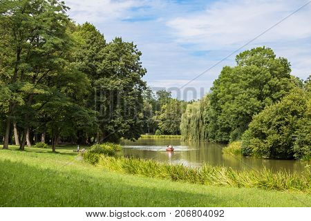 Garden landscape : lake is surrounded by a green lawn and old deciduous trees at sunny summer day. Boat with people in the middle of the lake . Old park Schoenbusch ( Schönbuch ) - english landscape garden Aschaffenburg Germany