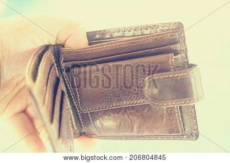 Empty open brown purse in one hand