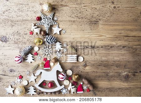 Christmas Decoration Forming Shape Of Christmas Tree. Decoration Like, Rocking Horse, Santa Hat, Fri Con And Christmas Ball Ornament. Aged Brown Wooden Background With Copy Space