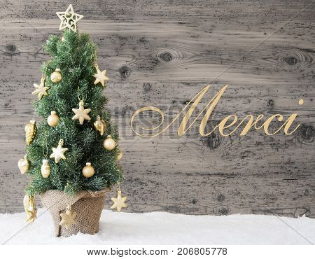 French Text Merci Means Thank You. Golden Decorated Christmas Tree With Gray Vintage Background. Rustic Wooden Style With Snow