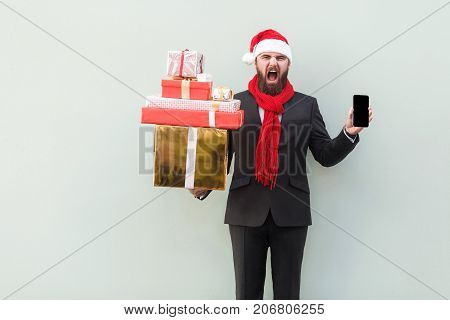 Anger Businessman Holding On Hands Gift Box And Phone. Looking At Camera With Roar Face.
