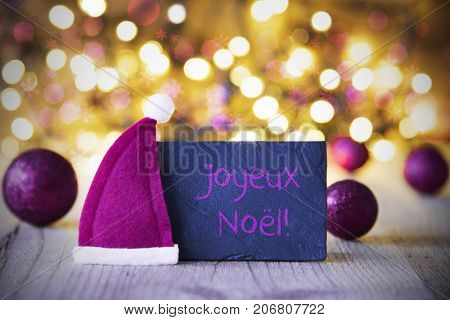 Plate With French Text Joyeux Noel Means Merry Christmas. Purple Christmas Ball Ornaments And Santa Claus Hat. Wooden Background With Lights