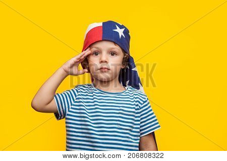 Little charming boy with American flag wrapped on head saluting and looking away on orange.
