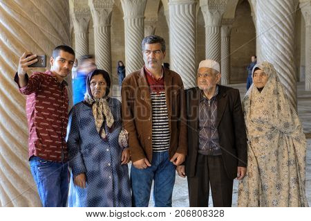 Fars Province Shiraz Iran - 19 april 2017: Tourist excursion to the Vakil mosque the Iranian family is photographed in the prayer hall.