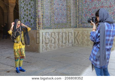 Fars Province Shiraz Iran - 19 april 2017: The girl photographer photographing the model in the Iranian national costume while near the entrance to the mosque.