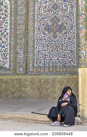 Fars Province Shiraz Iran - 19 april 2017: Muslim woman wearing in Islamic clothing sits inner courtyard Vakil Mosque.