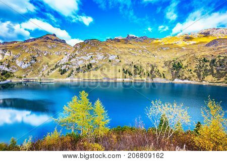 The concept of ecological tourism. The harmony of the Dolomites. Mountain Lake Lago di Fedaia, Dolomites. Glacial lake with clear cold water