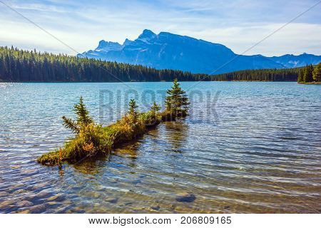 Charming little island near the shore. The pure turquoise water of the lake reflects coniferous forests. The  Lake Two Jack, gulf of lake Minnewanka. The concept of ecological and active tourism