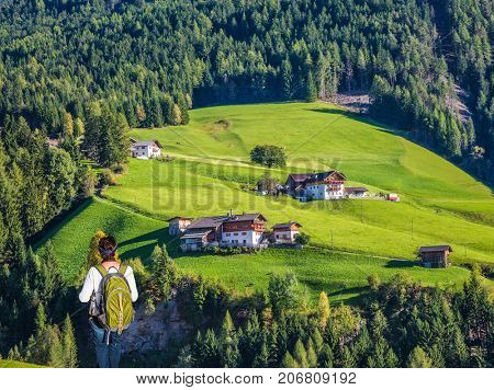 Warm autumn in the Val de Funes, Dolomites. Elderly woman - tourist with backpack travels in Tyrol. The concept of active and ecotourism