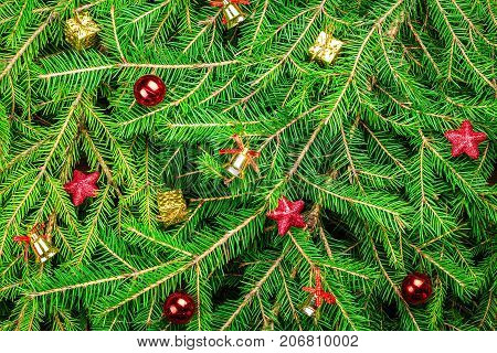 Bright festive Christmas and New Year background: green fresh fir branches and decoration in the form of golden bells with red ribbons, red balls and stars and gift boxes in a golden wrapper