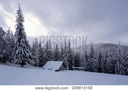 Picturesque winter landscape with huts snowy mountains and forest. Winter landscape for leaflets.