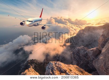 Landscape With White Passenger Airplane, Mountains, Sea And Orange Sky
