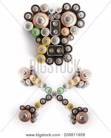 Skull and crossbones made from various used batteries. Environmental pollution concept. Isolated on white.