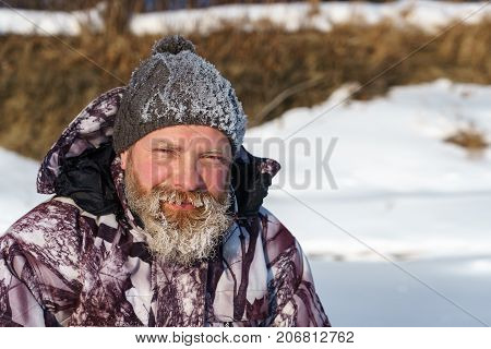 One Euriopean Bearded Fisher Man Or Hunter With Ice And Hoarfrost On Beard Is Looking To The Camera