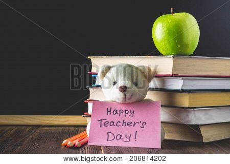 Concept Of Teacher's Day. Objects On A Chalkboard Background. Books, Green Apple, Bear With A Sign: