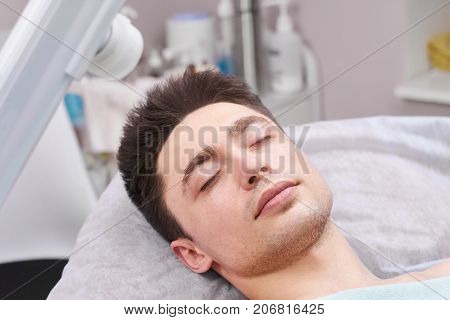Man in the hospital. Young male with eyes closed. Facts about general anesthesia.