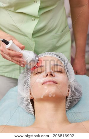 Female face, rf skin tightening. Young woman in facial mask.