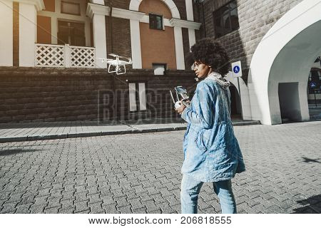 Pensive young biracial curly lady is driving white modern drone using remote controller having screen for showing video from quadrupter's camera while standing on pavement of urban street on sunny day