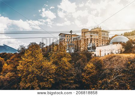 Autumn landscape in resort district of Sochi city Russia: yellow trees ropeway above them with one modern funicular cabin and retro one dry grass; resort buildings and hills in background