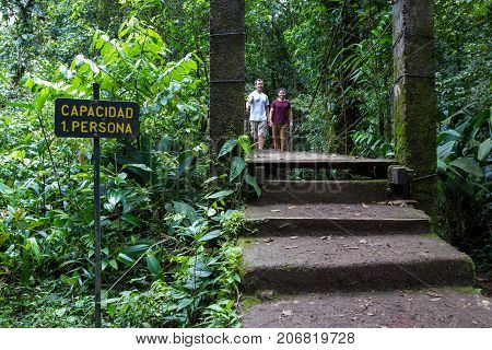 friends walking on a hanging bridge in the Tenorio National Park with lush green vegetation all around