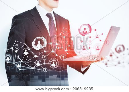 Side view of unrecognizable young businessman using laptop with abstract HR network. Hiring concept. Double exposure
