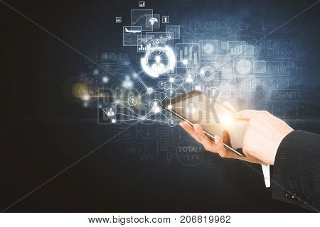 Side view and close up of businessman hands using tablet with digital business hologram on dark background. Device and hud concept. Double exposure