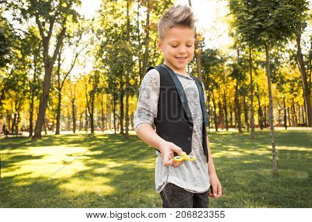 Beautiful and smiling boy in casual wearing with spinner in him hands looking at the toy and playing fidget toys
