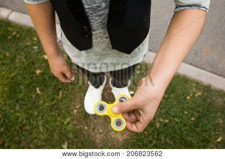 Close up. Boy's hands with spinner. Casual beautiful boy in style clothes with spinner