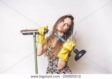 Frustrated young woman cleaning with mop and plunger
