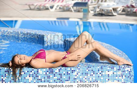 Beautiful young woman lying on the edge of swimming pool at resort