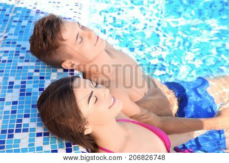 Happy young couple in swimming pool at resort