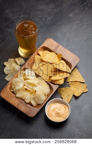 Beer In Glasses Closeup On The Concrete Table. Beer And Snacks Are Chips And Nachos With Cheese Souc