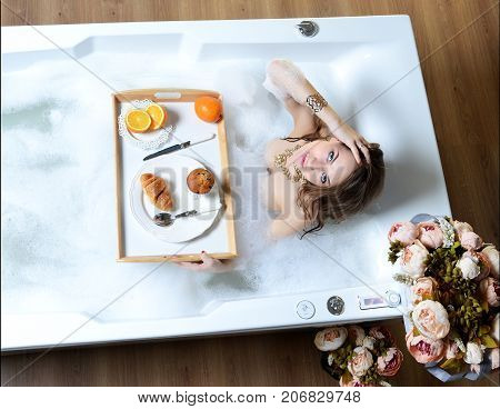 Luxury fashion woman in the morning take breakfast in hotel spa lying in bath tub with croissant muffin and orange