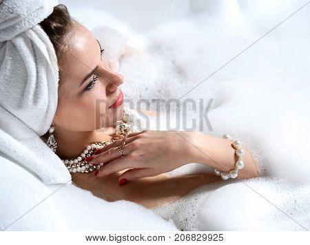 Luxury fashion woman with soft big towel in the morning hotel spa lying in bath tub thinking