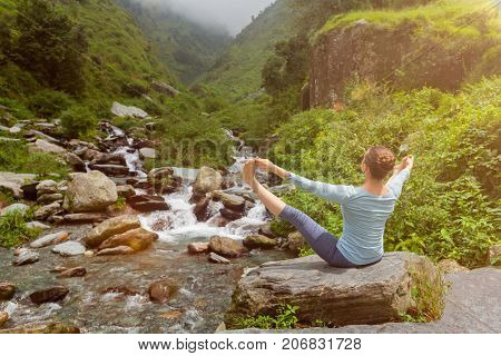 Woman doing Ashtanga Vinyasa Yoga asana Upavistha konasana outdoors at tropical waterfall