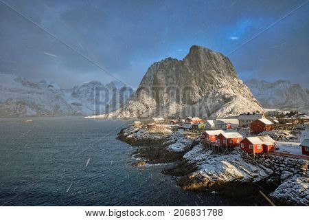 Hamnoy fishing village on Lofoten Islands, Norway with red rorbu houses. With falling snow blizzard in winter and rainbow