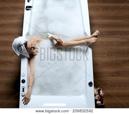 Luxury fashion woman with soft big towel in the morning hotel spa lying in bath tub thinking in big space room