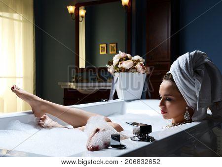 Luxury fashion woman with soft big towel in the evening in hotel spa lying in bath tub