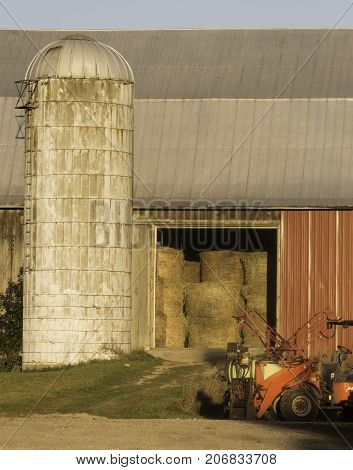 Barn doors open to reveal stacked hay bales