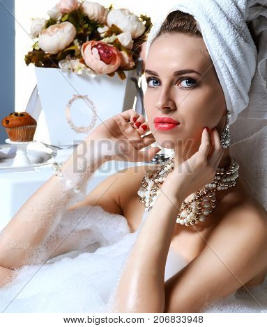 Luxury fashion woman in hotel spa lying in bath tub with bouquet of flowers and gold jewelry looking at the camera