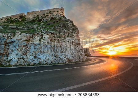 View of the Venetian castle on top of the hill, with perspective road at sunset Rethymno, Crete, Greece