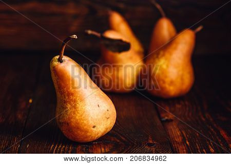 Golden Pear on Wooden Table and Few Pears on Backdrop.