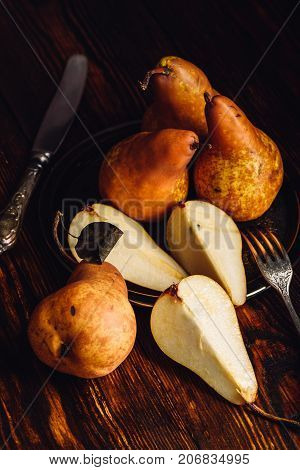 Few Golden Pears on Wooden Table with Sliced One Fork and Knife.Vertical Orientation.